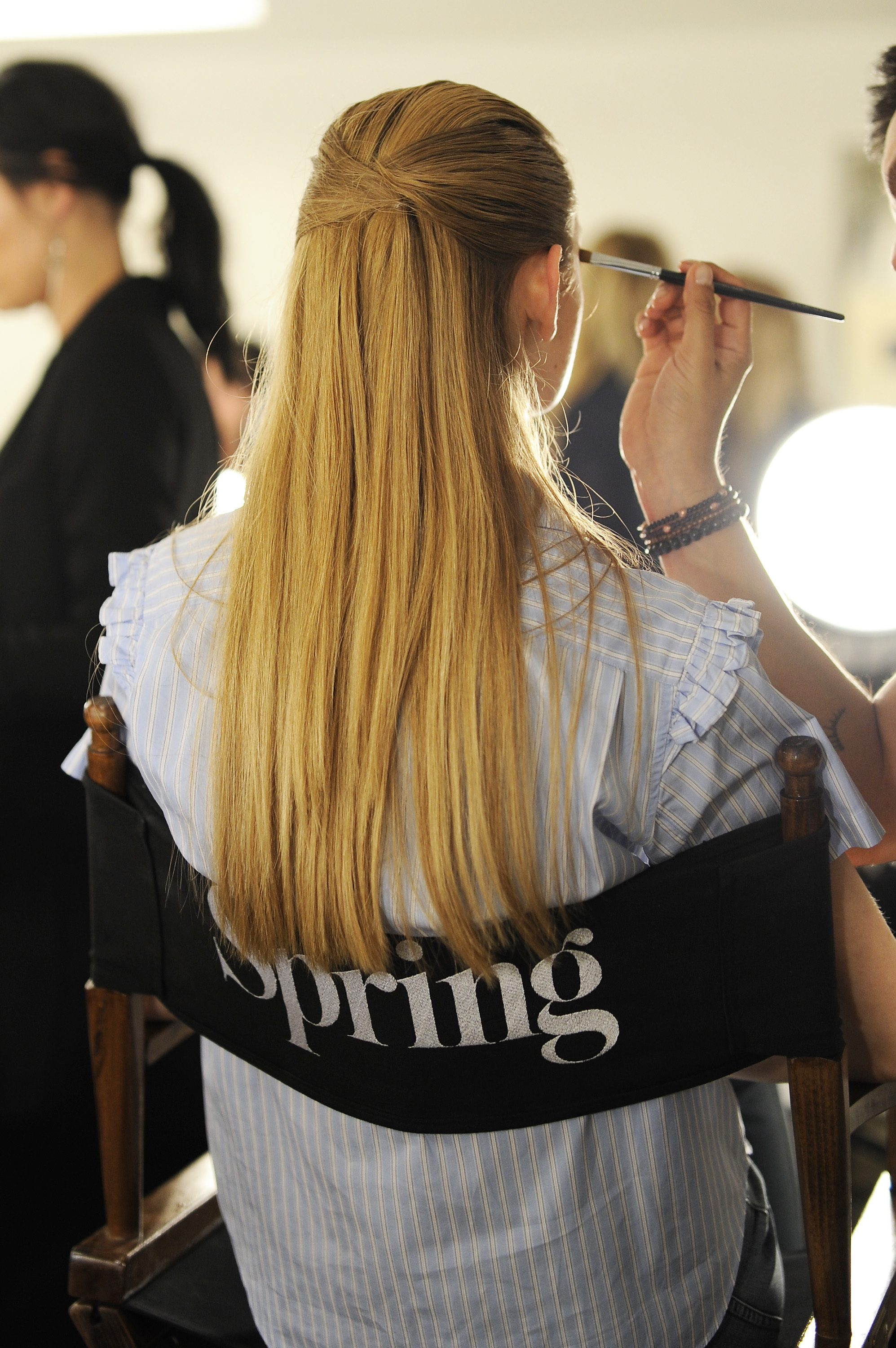 model backstage with dark blonde straight hair in a folded half up half down hairstyle
