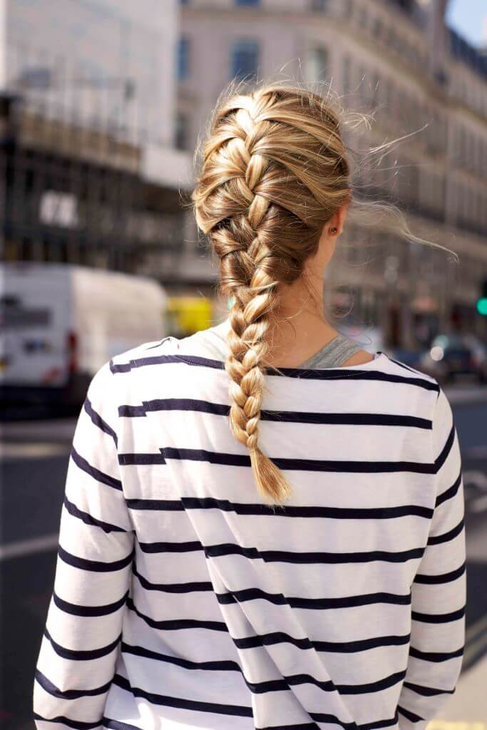 back view of a woman's hair with a golden-blonde-french-braid