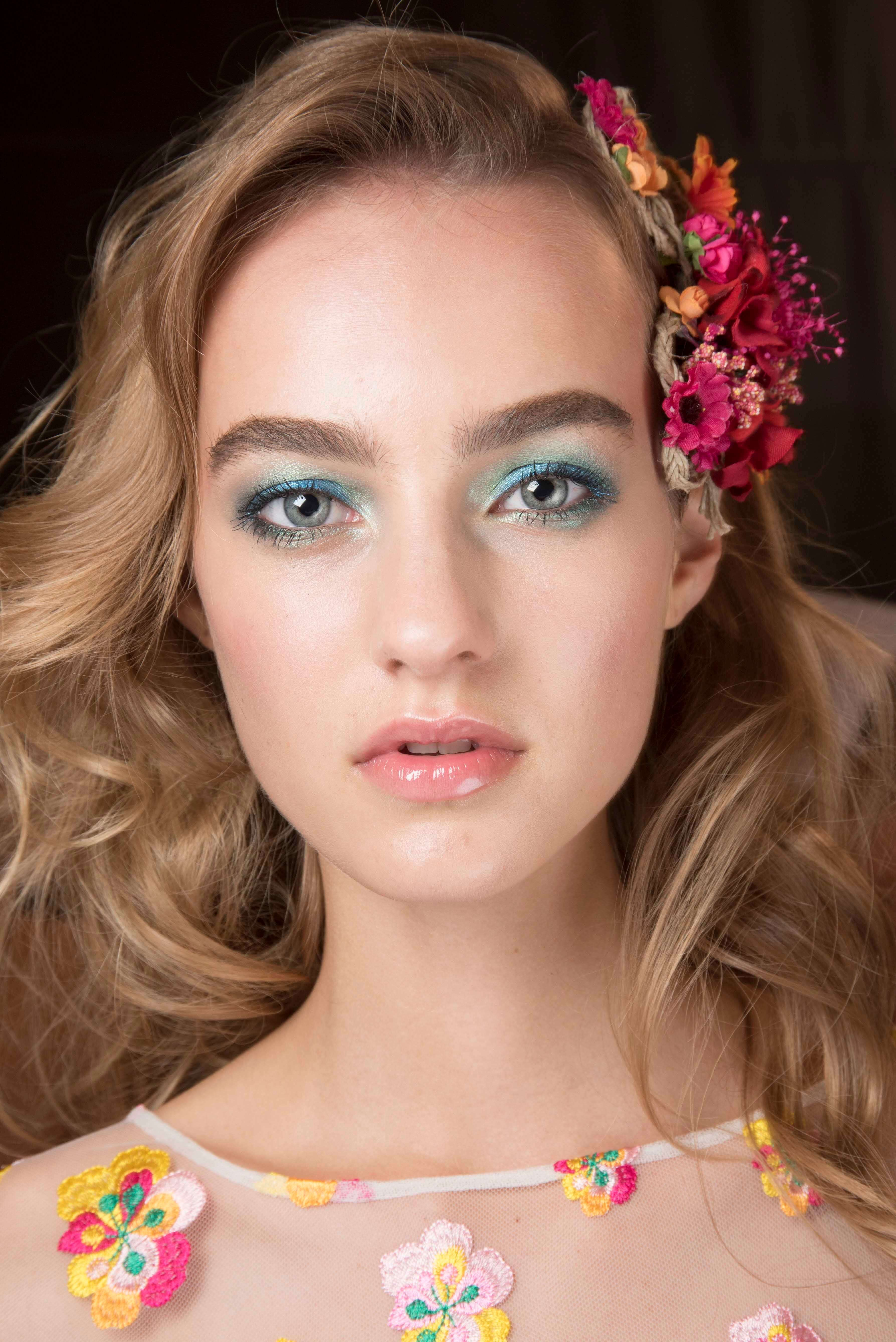 Curly prom hairstyles: Voluminous curls hairstyle accessorised with pink flowers.