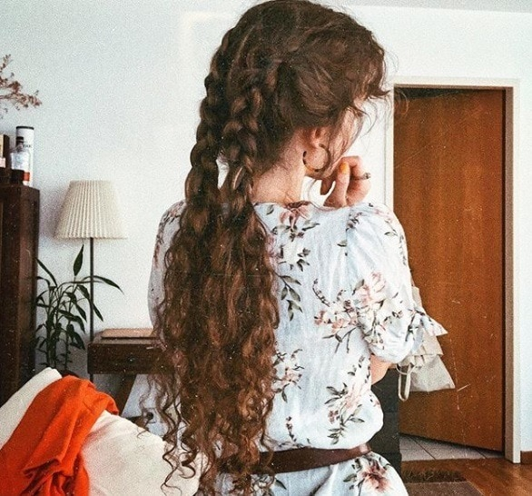 Long curly hair: Close up back shot of a woman with long chestnut brown curly long hair styled into half boxer braids, wearing a floral dress