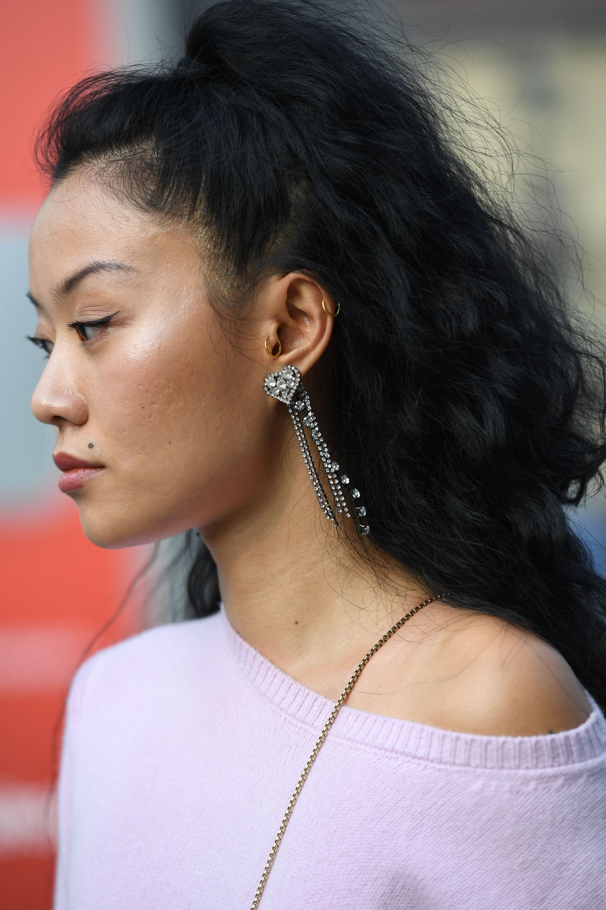 Long curly hair: Close up side shot of a woman with long dark brown curly hair styled into a half-up, half-down ponytail, wearing lilac jumper with drop earrings on the street
