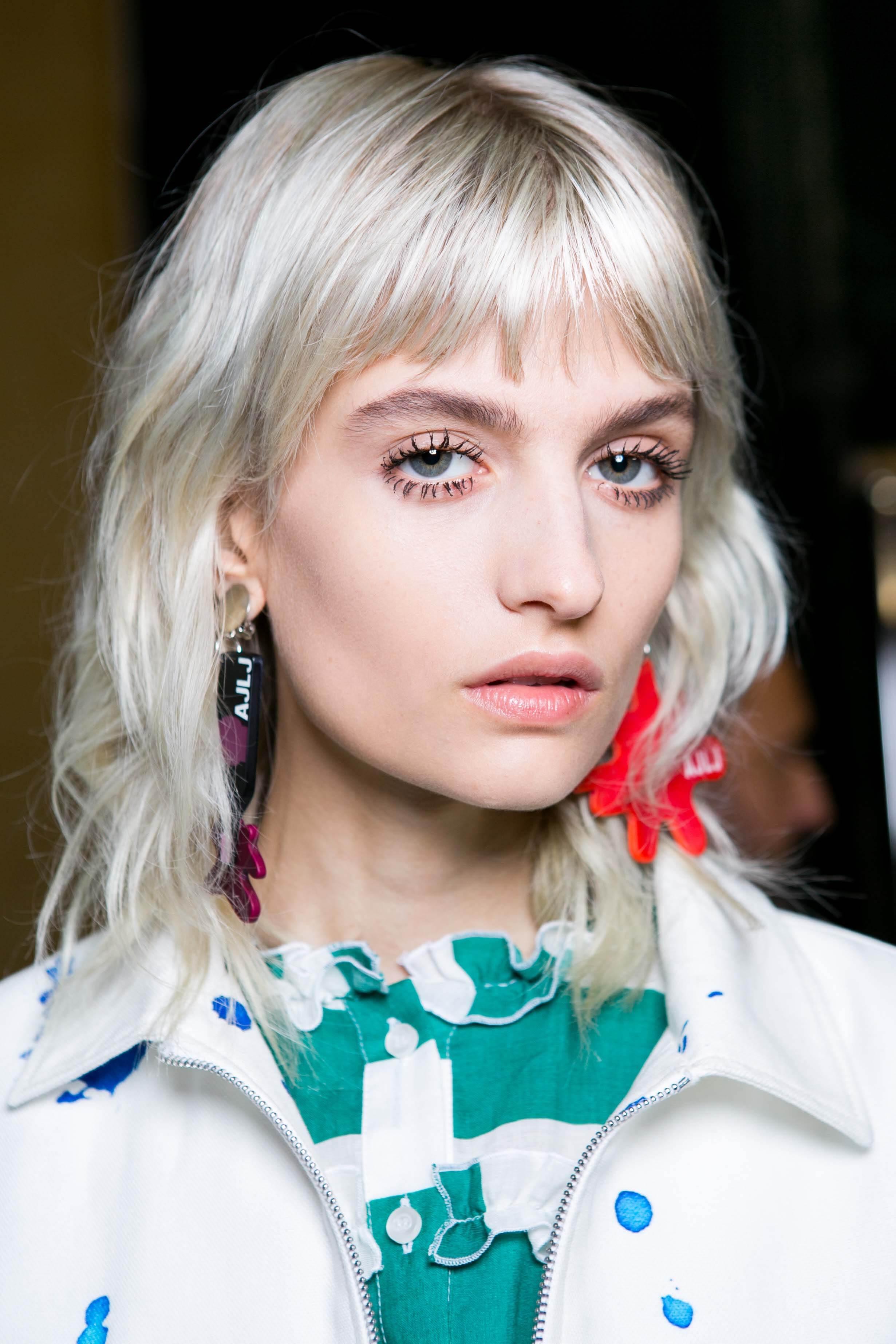 Woman with icy blonde shag cut hair bleaching