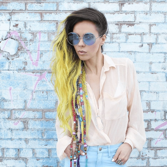 Boho hairstyles: Woman with long ombre yellow festival hair with hair wraps standing against a blue brick wall
