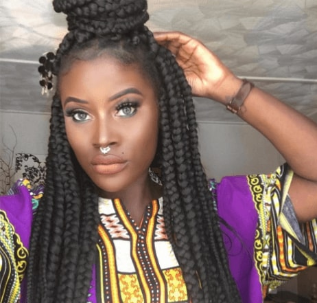 selfie of a girl with long brunette box braids in a half up half down bun hairstyle wearing a purple and gold patterned tunic top