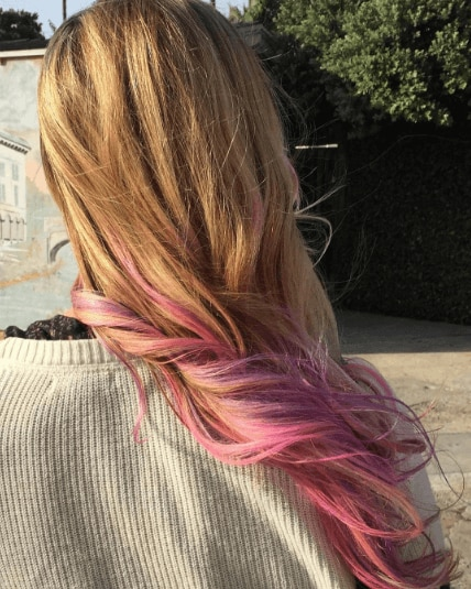 close up shot of woman with pink ombre hair tips, wearing white top and posing outside for Instagram