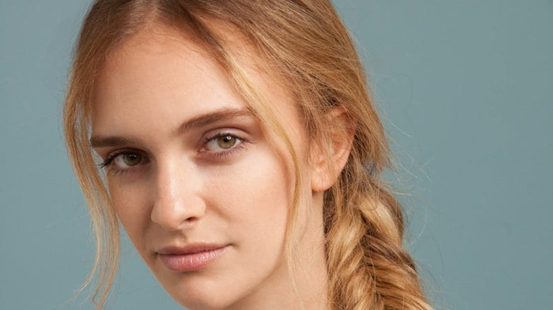 Inverted fishtail braid tutorial: A young blonde woman with an inverted fishtail braid