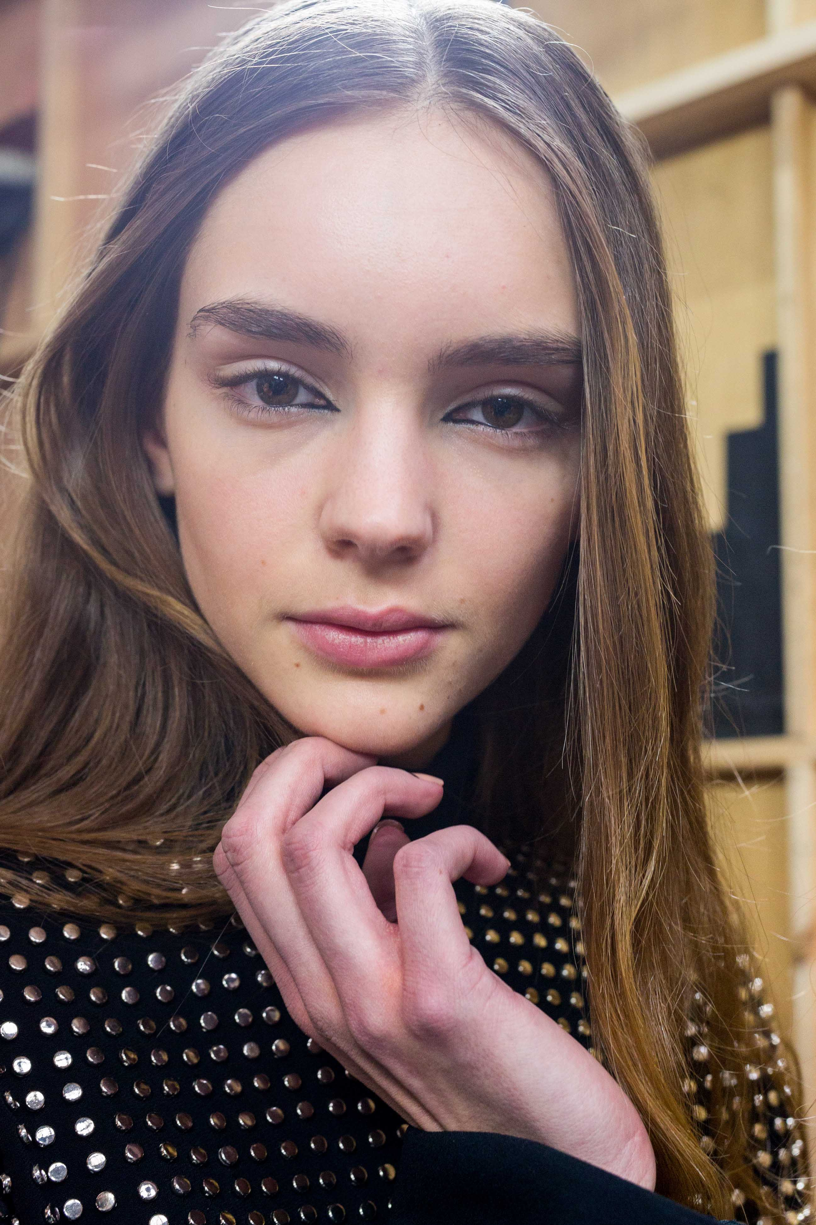 Hair straightening treatment: Model with straight brown hair touching her chin wearing a black studded top backstage at David Korma FW16 show.