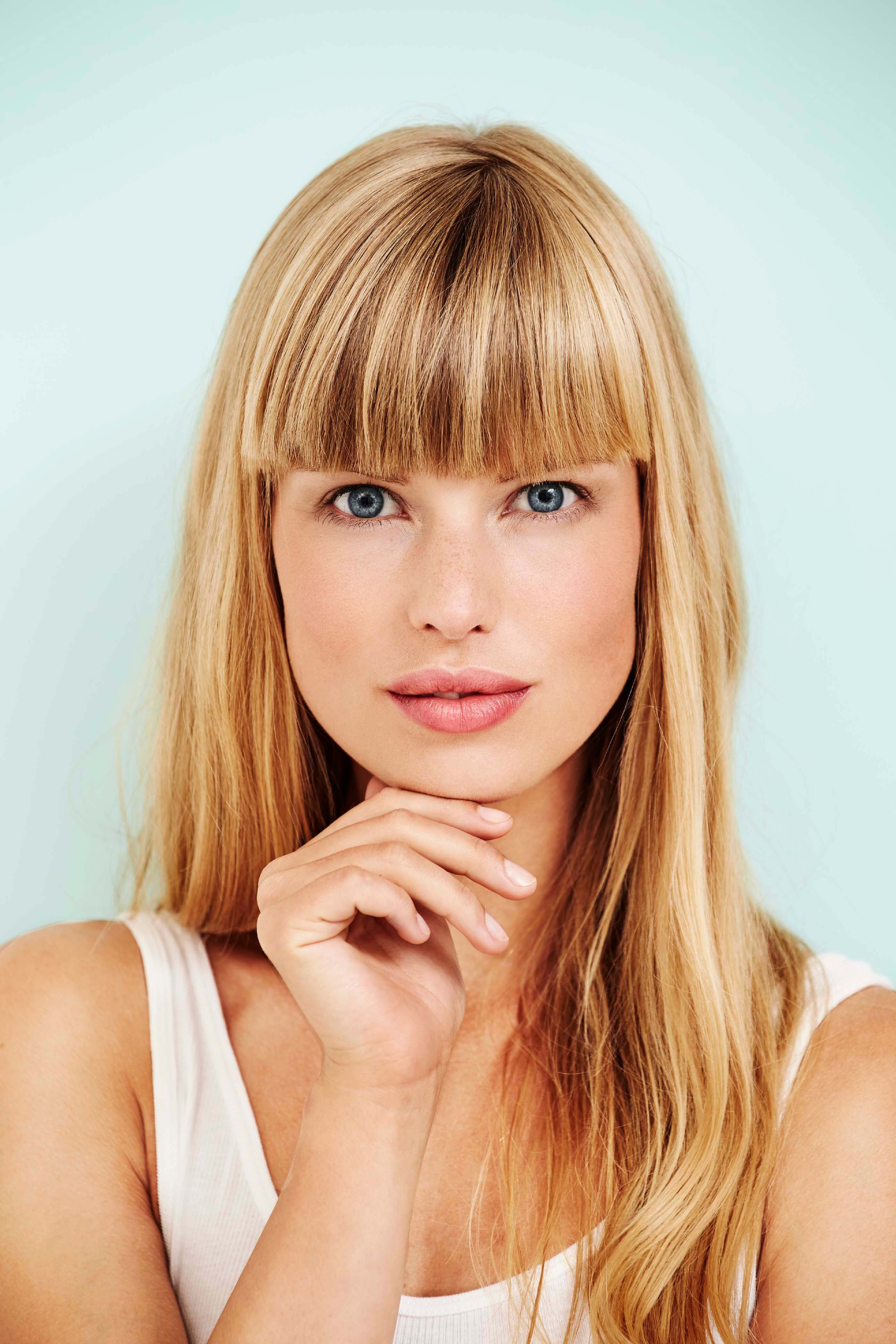 model with blonde hair wearing a blunt fringe