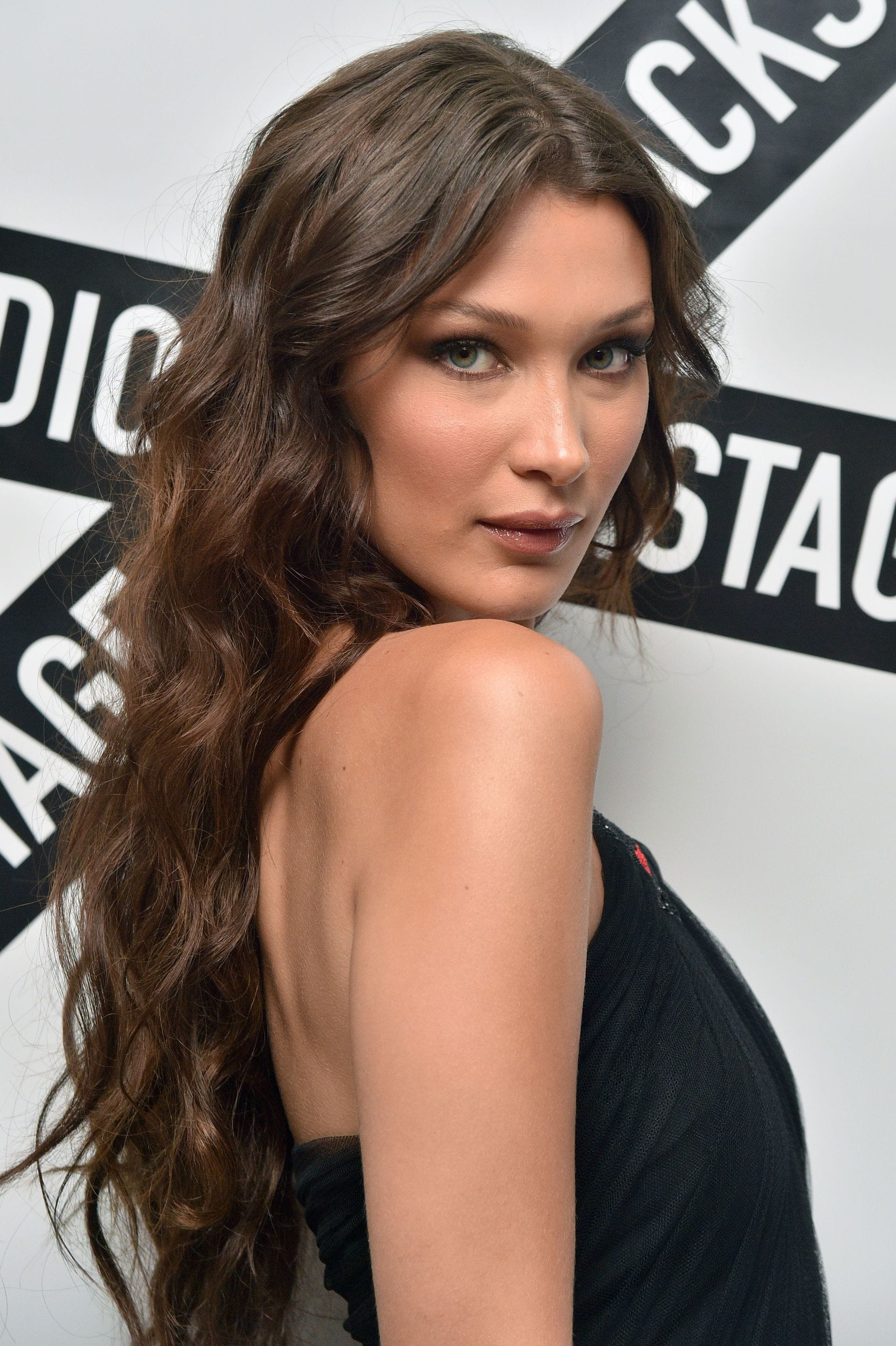 Long curly hair: Close up shot of model Bella Hadid with long curly chocolate brown hair, wearing black and posing at a Dior show
