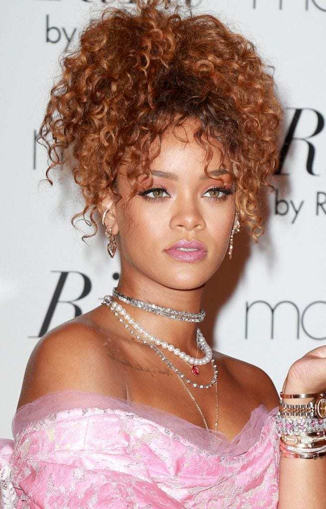 Long curly hair: Close up shot of Rihanna with long curly hair styled into a curly updo, wearing a necklace and Bardot cut dress