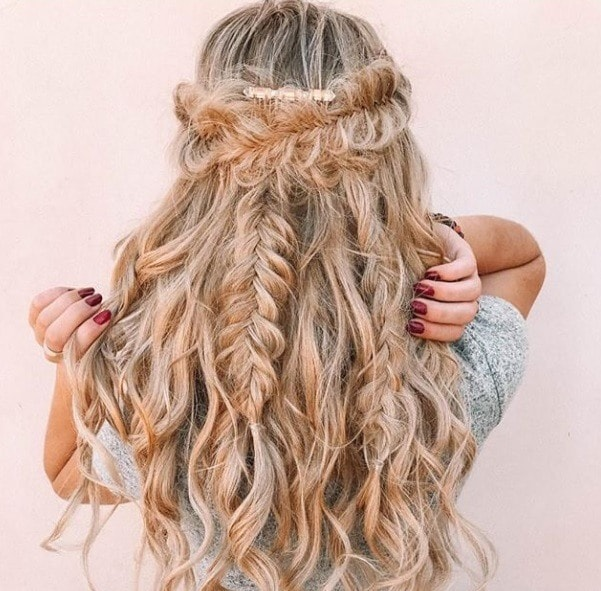 Long curly hair: Backshot of a woman with ashy blonde long curly hair in a half up half down fishtail braid.