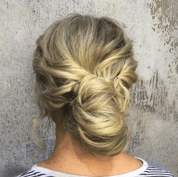 back view of a womans head with a low messy bun