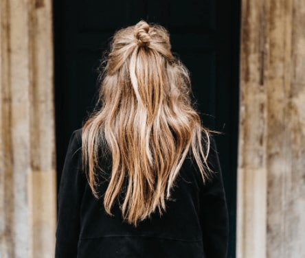 back view of a womans head with golden hair in a half down top knot