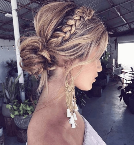 side view of a woman with her hair in a low golden blonde hair in a bun with a braid
