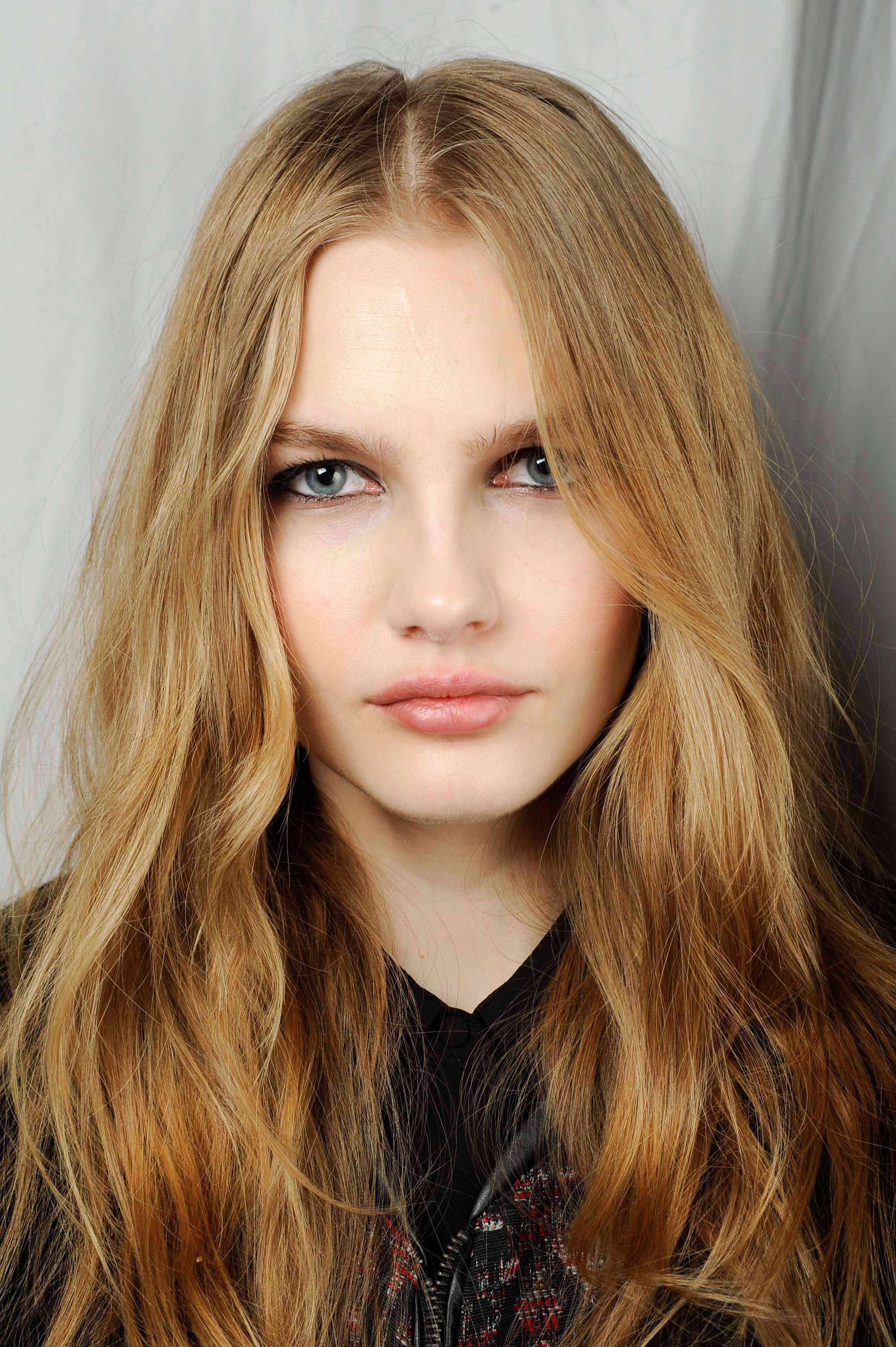 Shades of blonde hair: Woman with wavy warm blonde long hair wearing a black top.