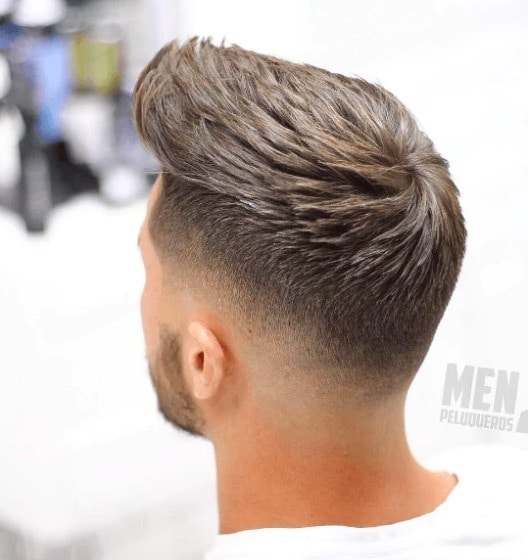 Hairstyles for men with thin hair: Man with a peak hairstyle on brown hair.