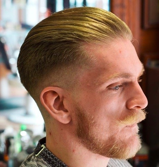Hairstyles for men with thin hair: Man with brushed back ginger hair and a trimmed beard and mustache