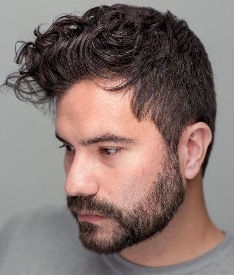 Hairstyles for men with thin hair: Man with dark hair and a full messy textured quiff