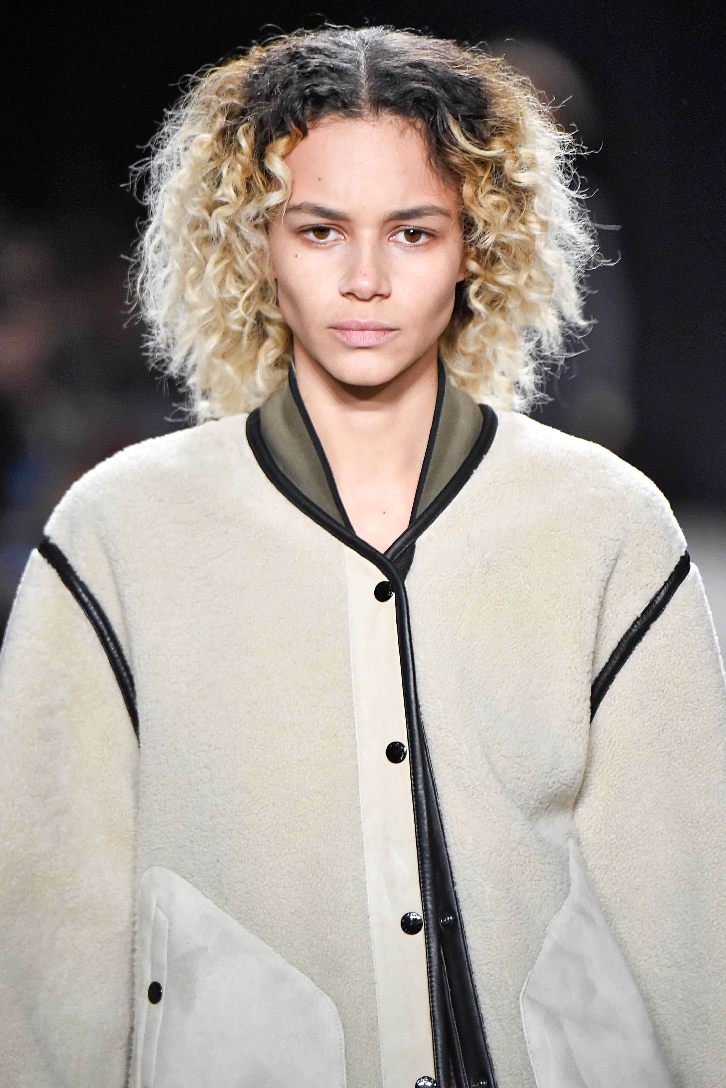 Shades of blonde hair: Woman with platinum blonde naturally curly hair with dark brown roots on runway wearing a bomber jacket.
