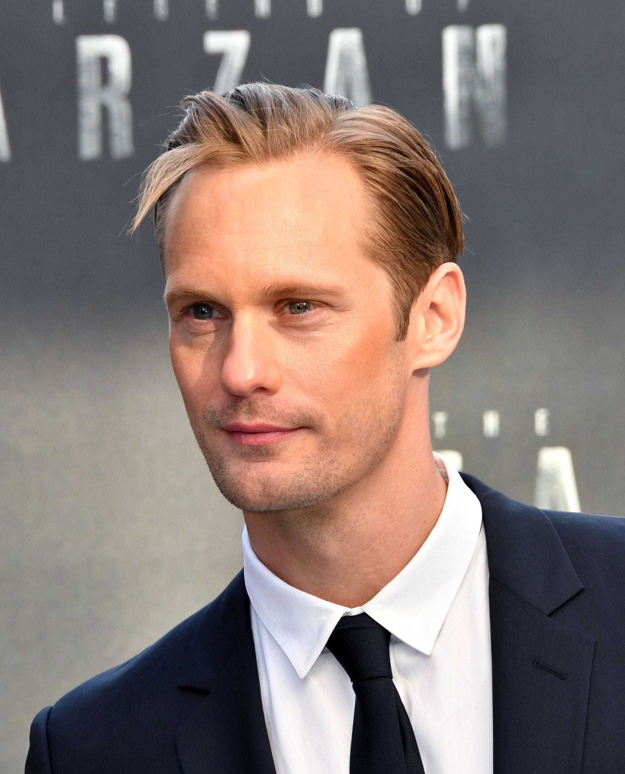 Hairstyles for receding hairline: Close-up of Alexander Skarsgard with blonde hair in a piecey side parted comb over style
