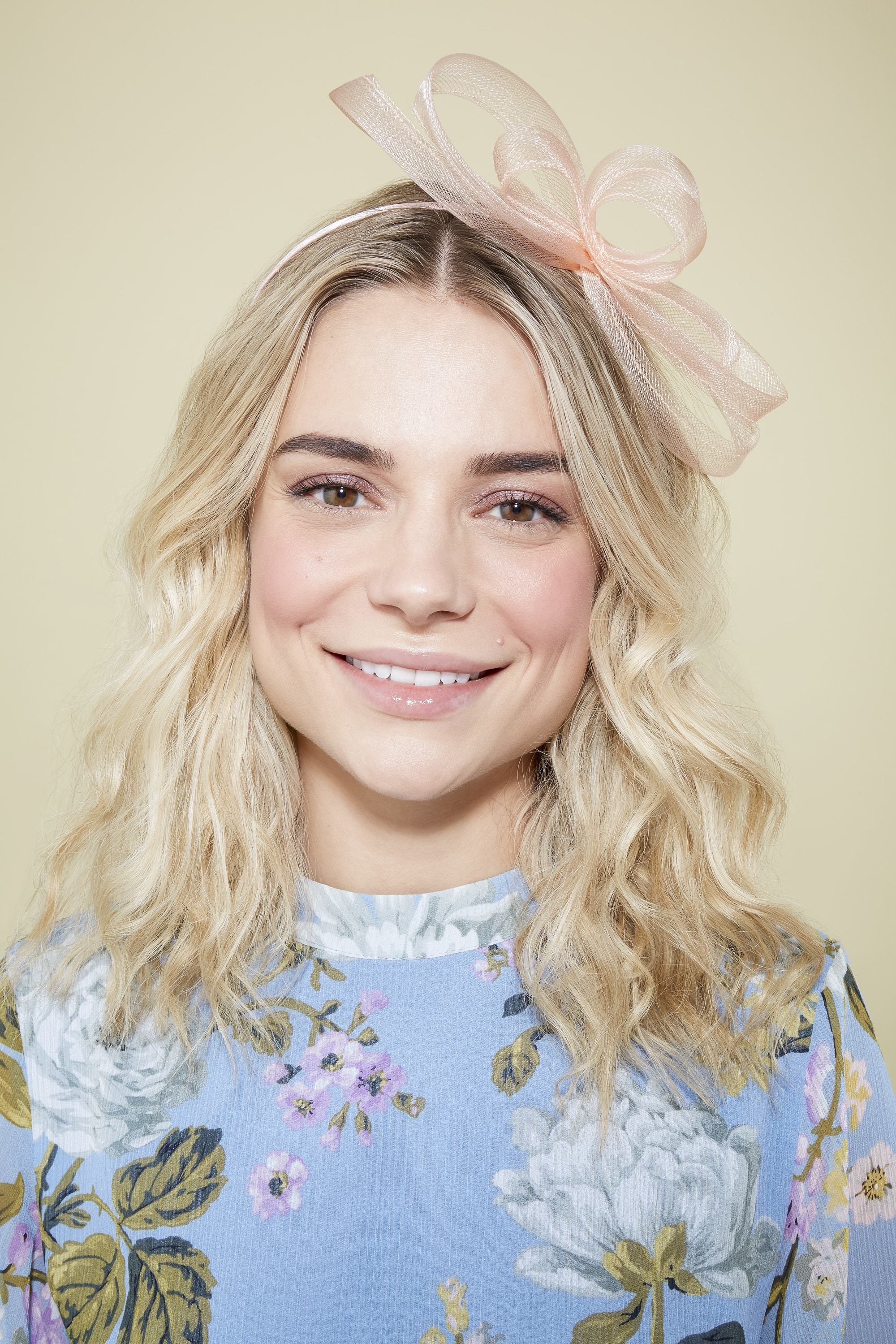 blonde model with blonde medium length hair styled in beach waves wearing a pink formal headpiece and light blue floral top