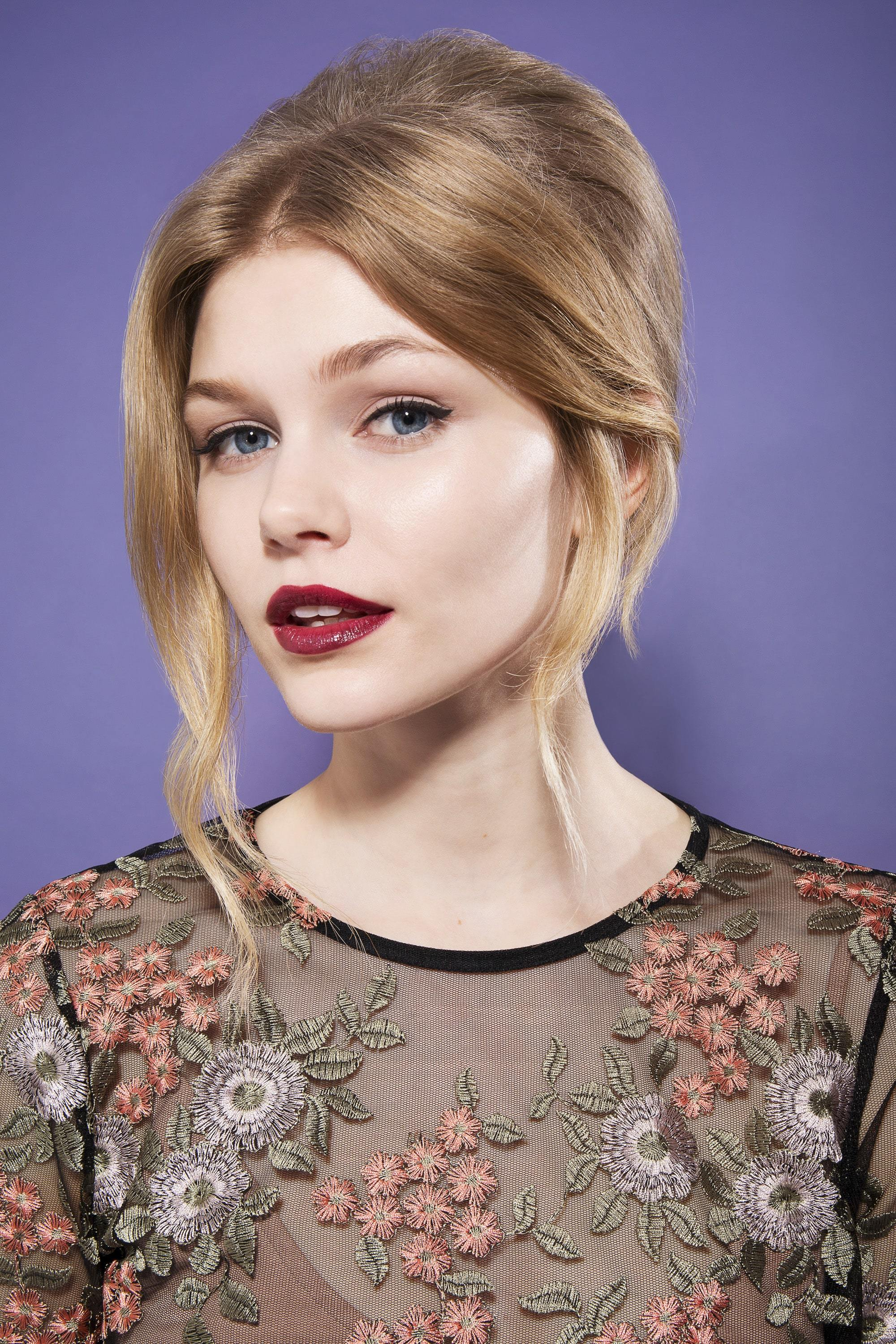 blonde model with straight and smooth hair in high beehive with loose sweeping long fringe wearing sheer floral top and dark red lipstick