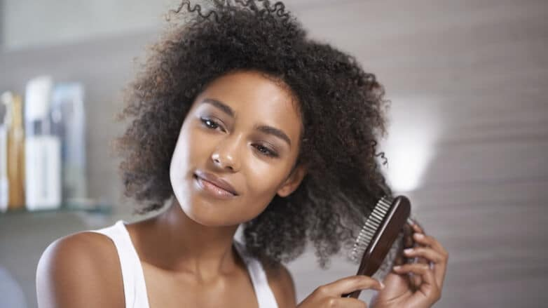 Black woman using a natural bristle hair brush