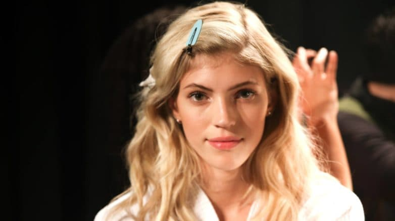 blonde model backstage with wavy hair with hair clips in her fringe