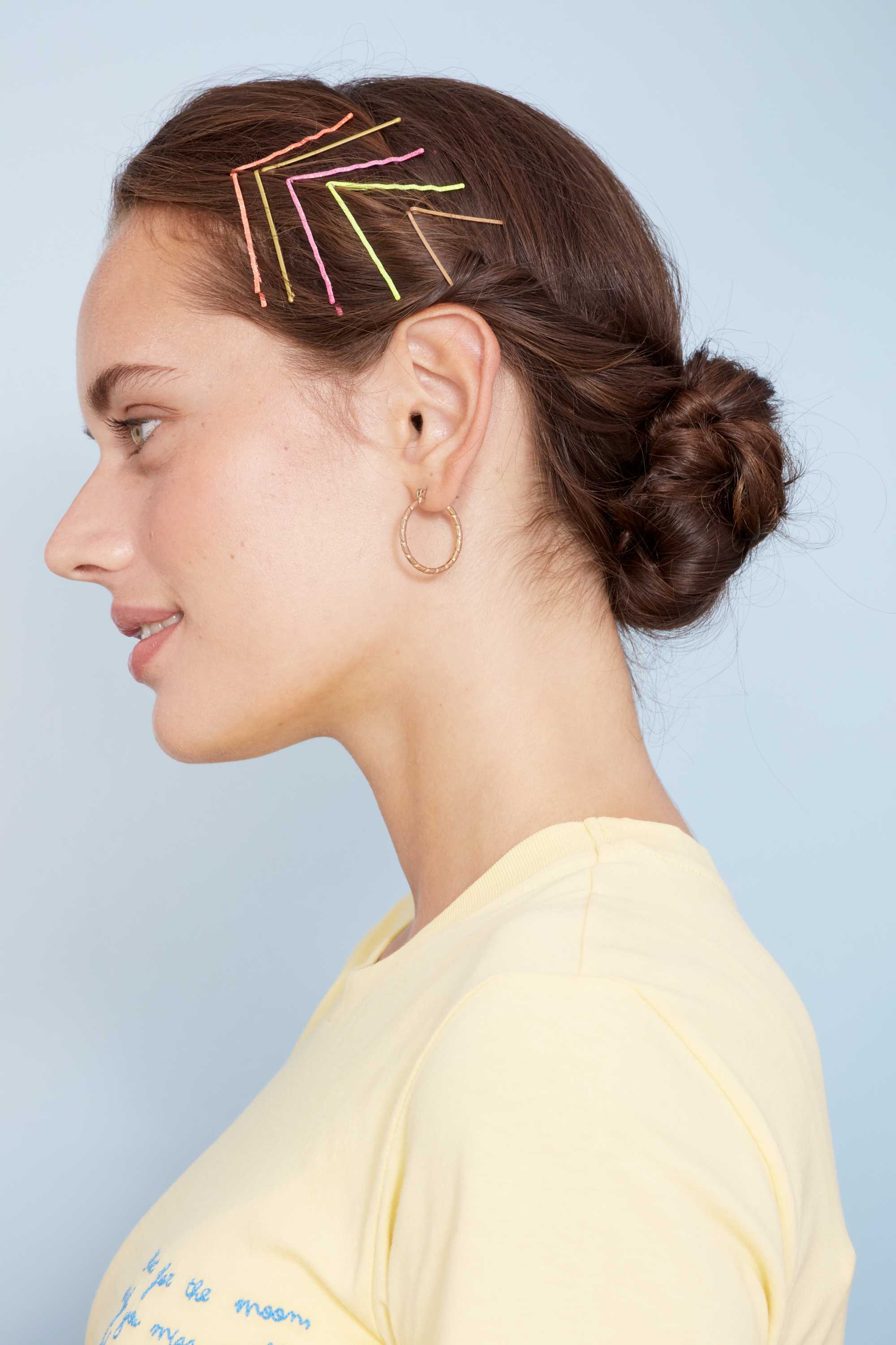 Bobby pin hairstyles: Close up shot of a woman with chestnur brown hair styled into a low bun with bobby pins styled into an arrow on the side of her hair, posing in a studio setting