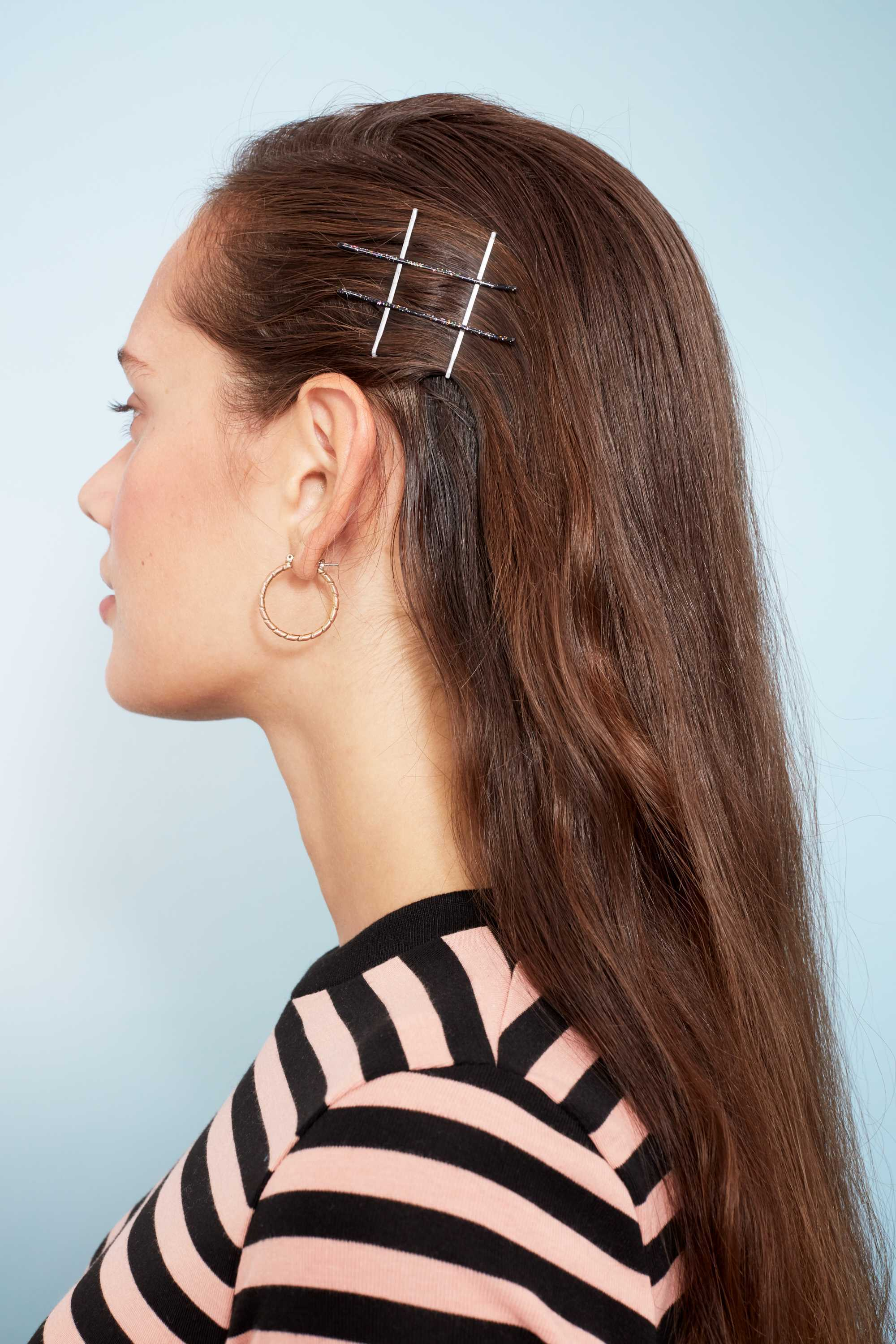 Bobby pin hairstyles: Close up shot of a woman with long chestnut brown hair styled with bobby pins shaped into a hashtag sign on one side of her hair. wearing stripes and posing in a studio setting