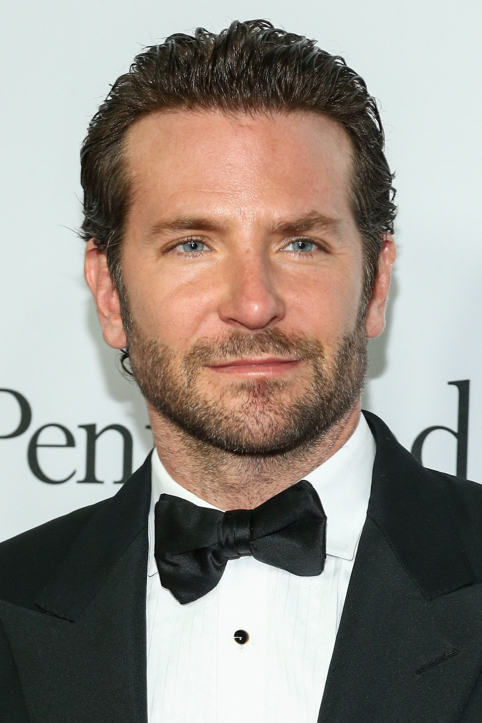 Hairstyles for receding hairline: Headshot of Bradley Cooper with combed back dark flow hair, wearing a tux and black bow tie