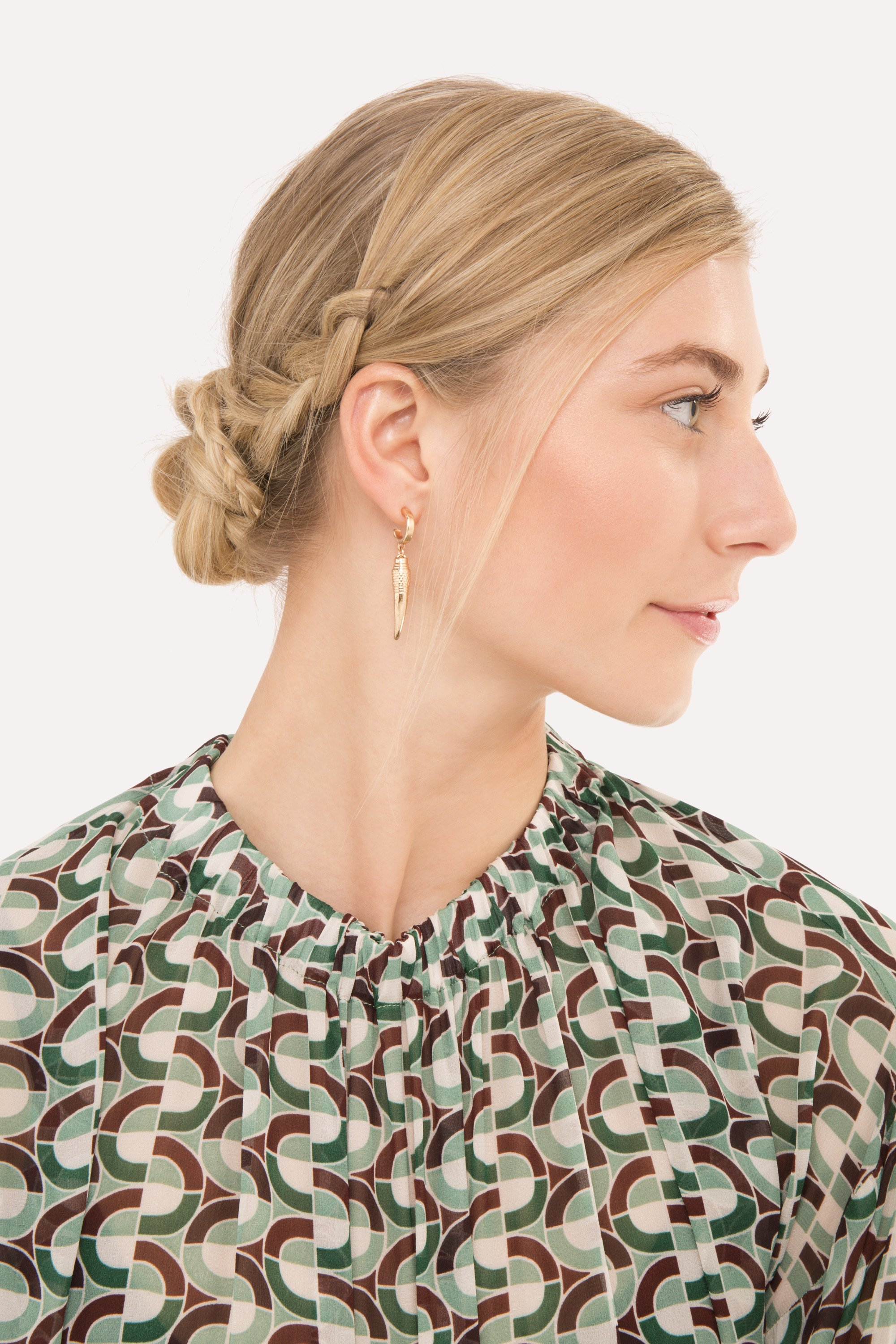 side view of model with straight blonde hair styled in a low bun with a braid detail on the side