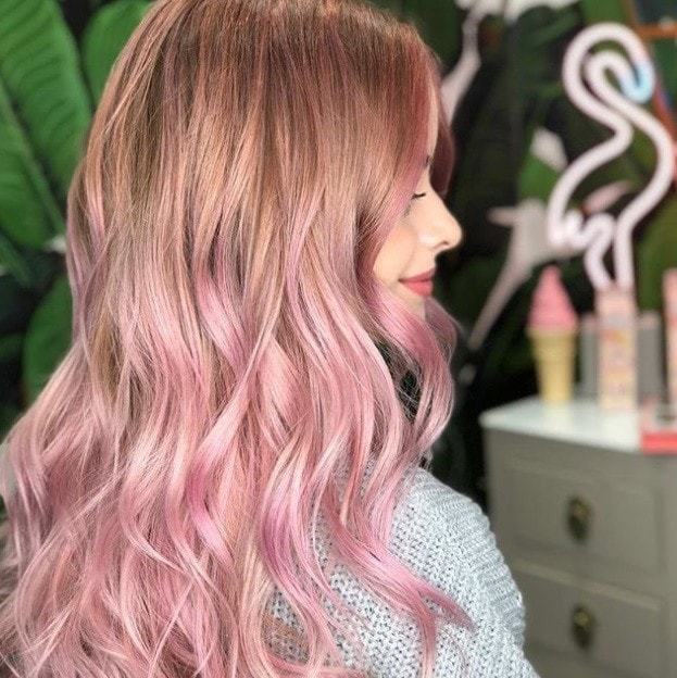 close up shot of woman with blonde hair with pink ombre ends, wearing a pastel jumper