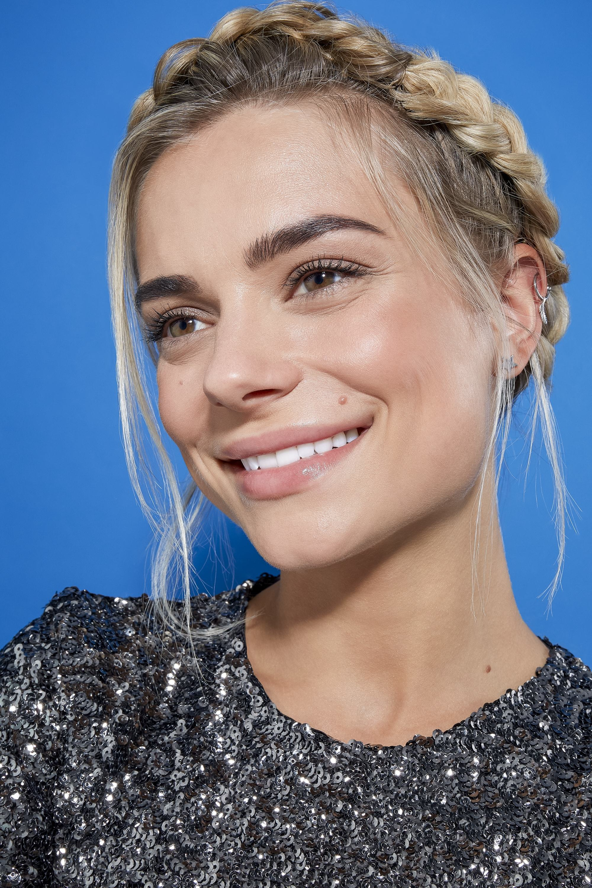 blonde model with straight hair styled in a crown braid with loose strands for a romantic feel