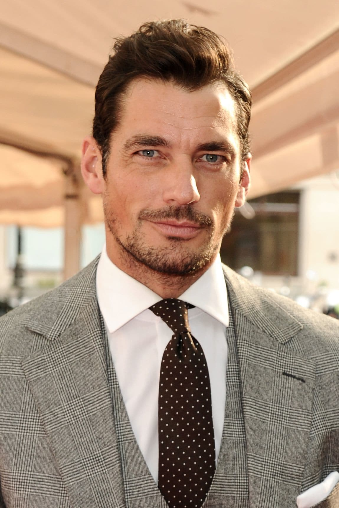 Hairstyles for receding hairline: Headshot of David Gandy with brown hair in a short brush back hairstyle