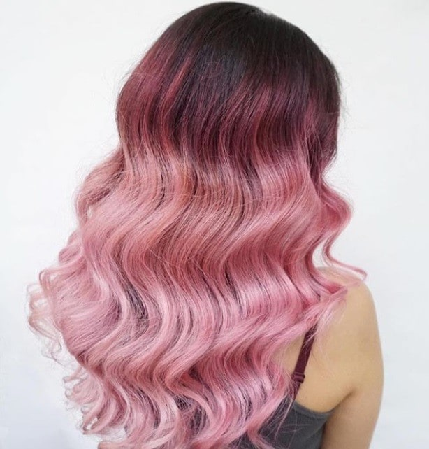 back shot of woman wavy long hair with candyfloss pink ombre melt, posing in a salon