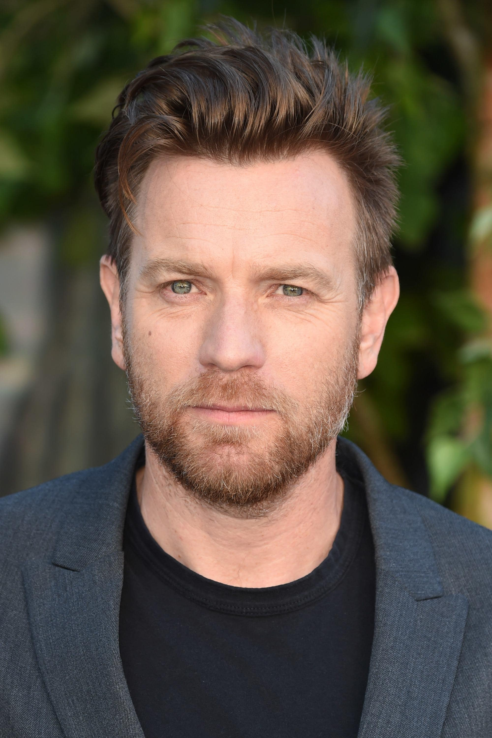 Hairstyles for receding hairline: Close-up headshot of Ewan McGregor with brown hair in a soft pomp style