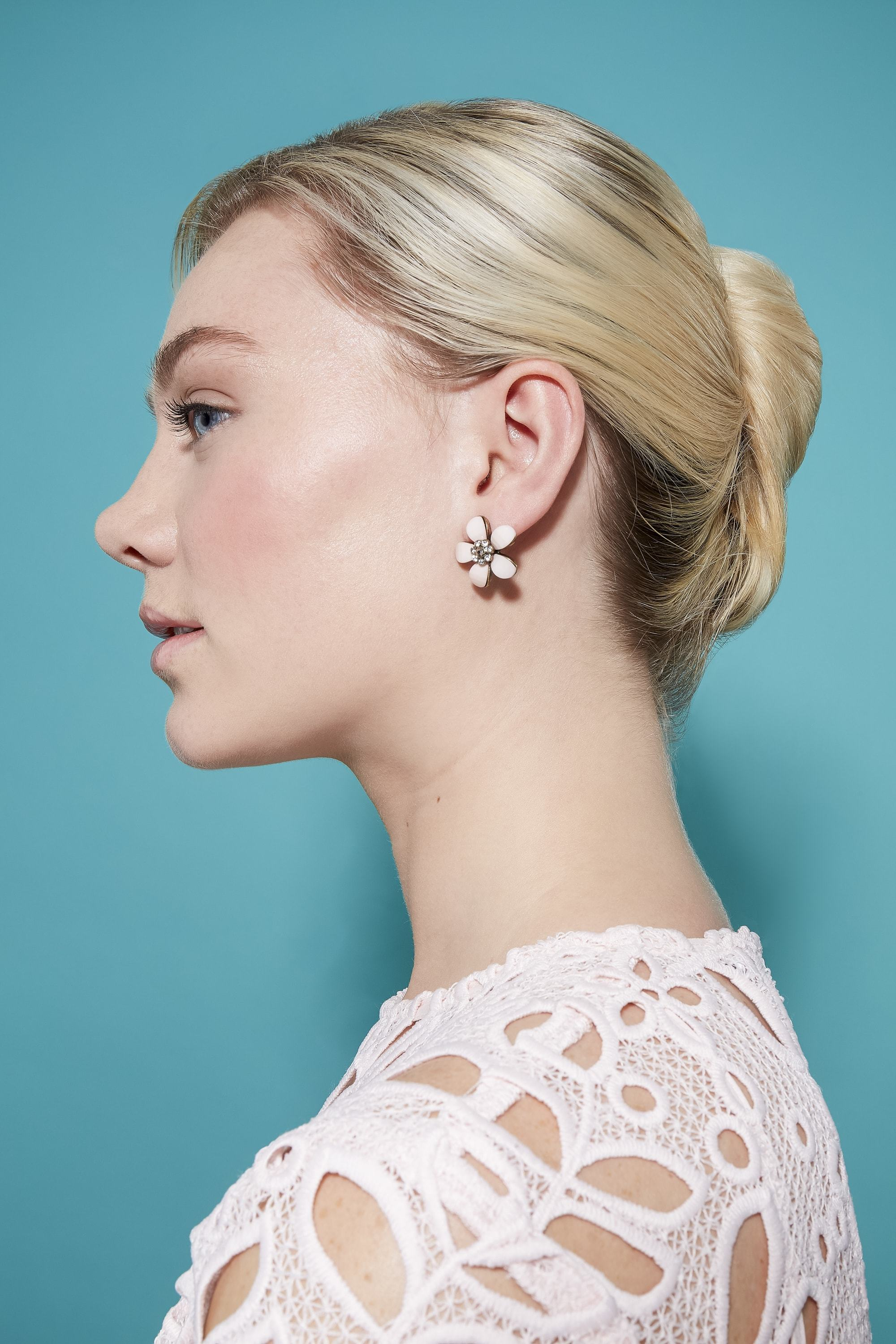side view of model with blonde hair styled into a french twist updo wearing a white top