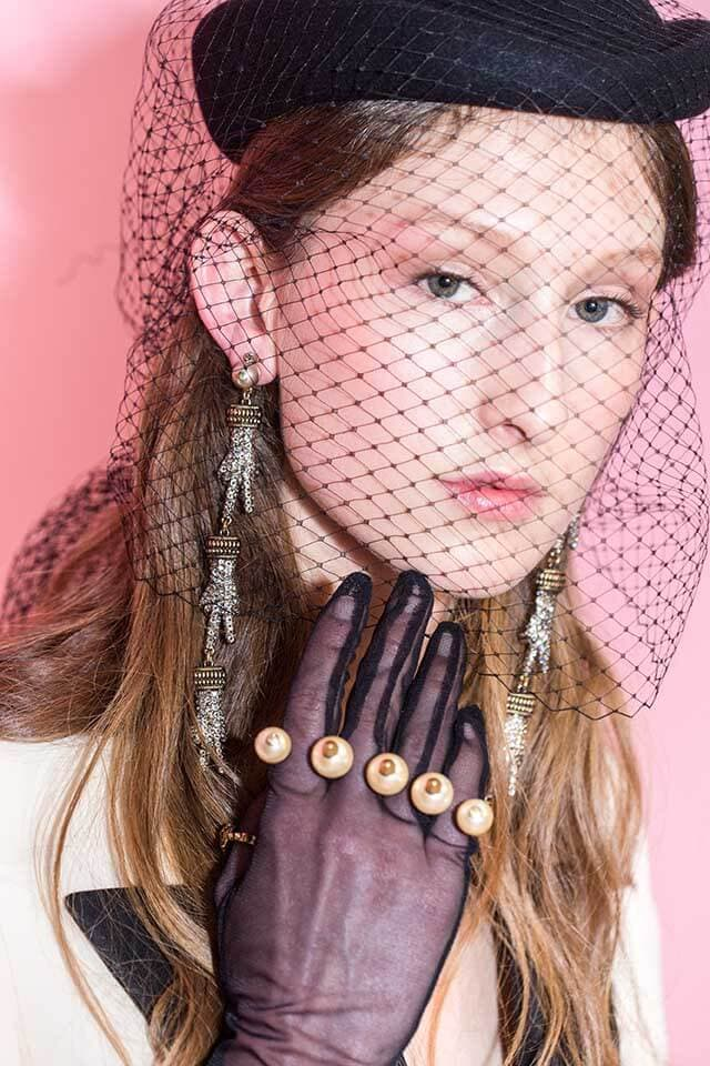 model at the Gucci AW16 show wearing a black hairnet iver her mousey brown hair with long earrings and a purple embellished glove