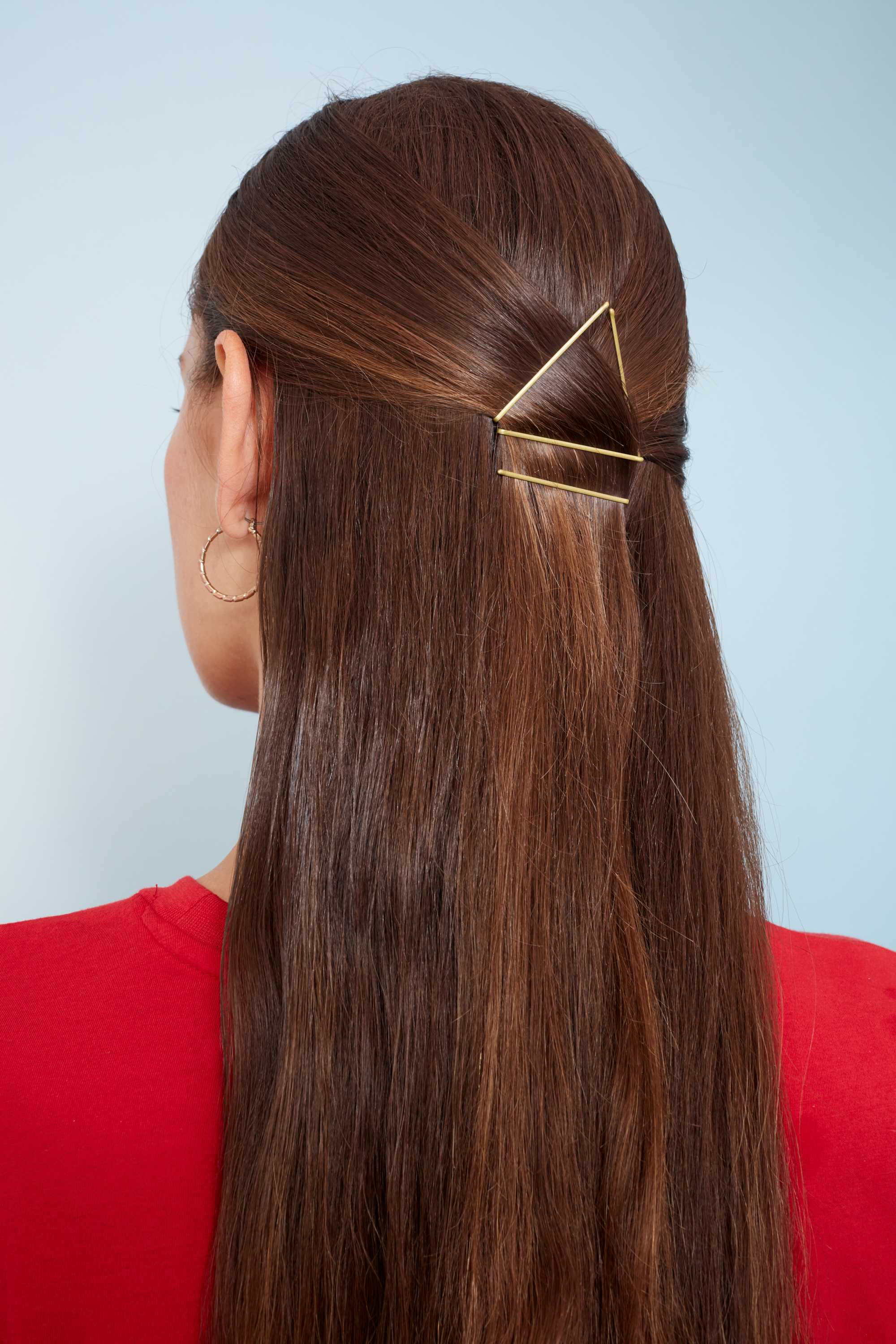Bobby pin hairstyles: Close up shot of a woman with long chestnut brown hair styled into a half-up, half-down hairstyle with bobby pins styled into a triangular shape