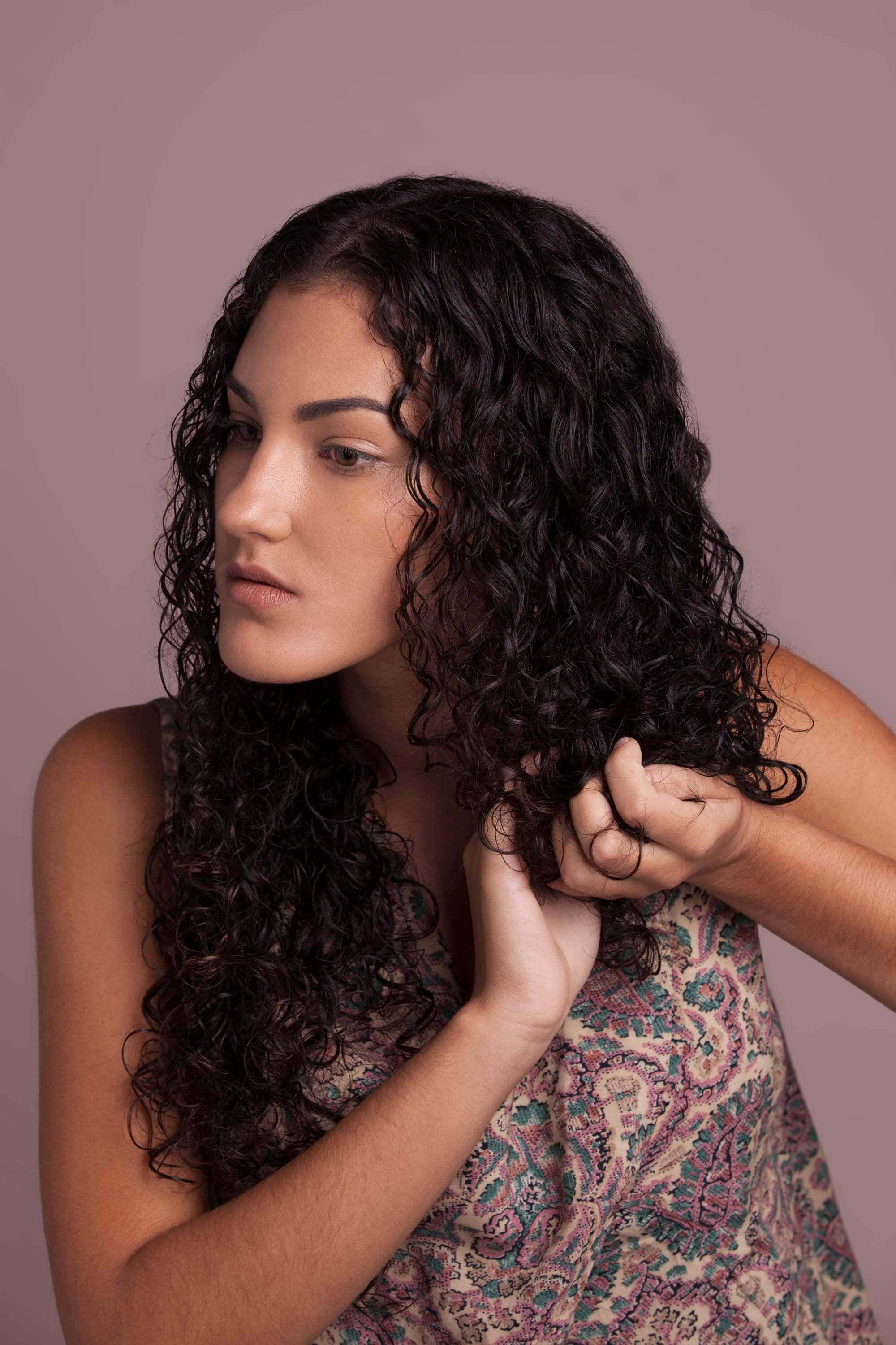 Woman with brunette curly hair scrunching her hair in her hands