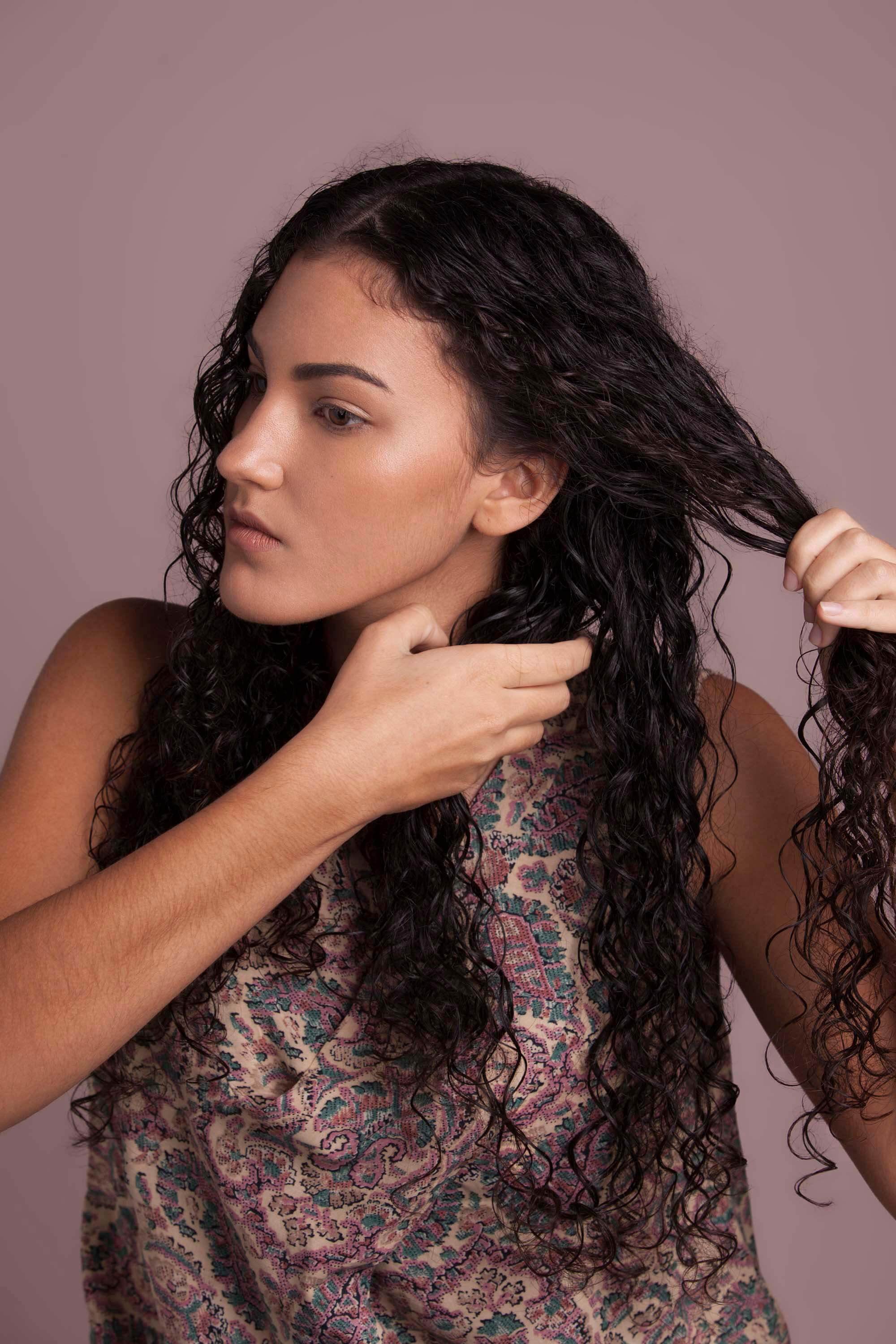 Woman with brunette curly hair sectioning her hair