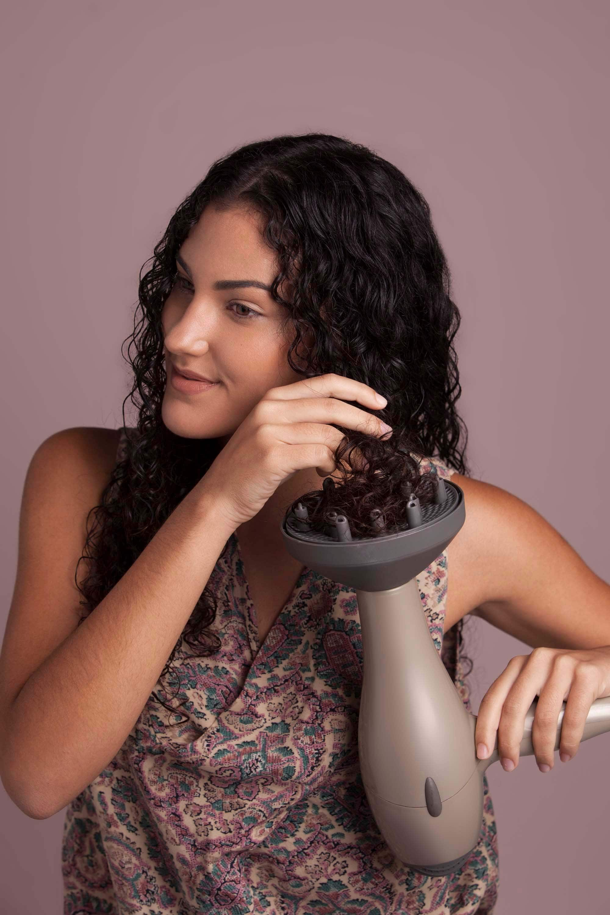 Woman with brunette curly hair putting her hair into a hairdryer diffuser