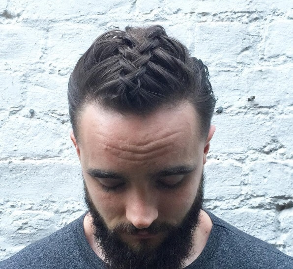 front view of a man with dark man braids and bun