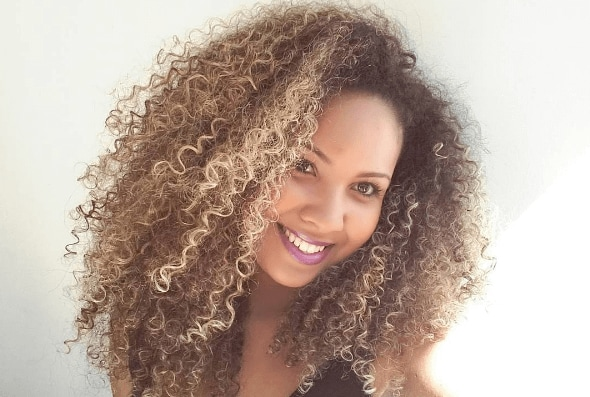 image of a woman with natural curly hair worn in twistouts with blonde highlights worn throughout