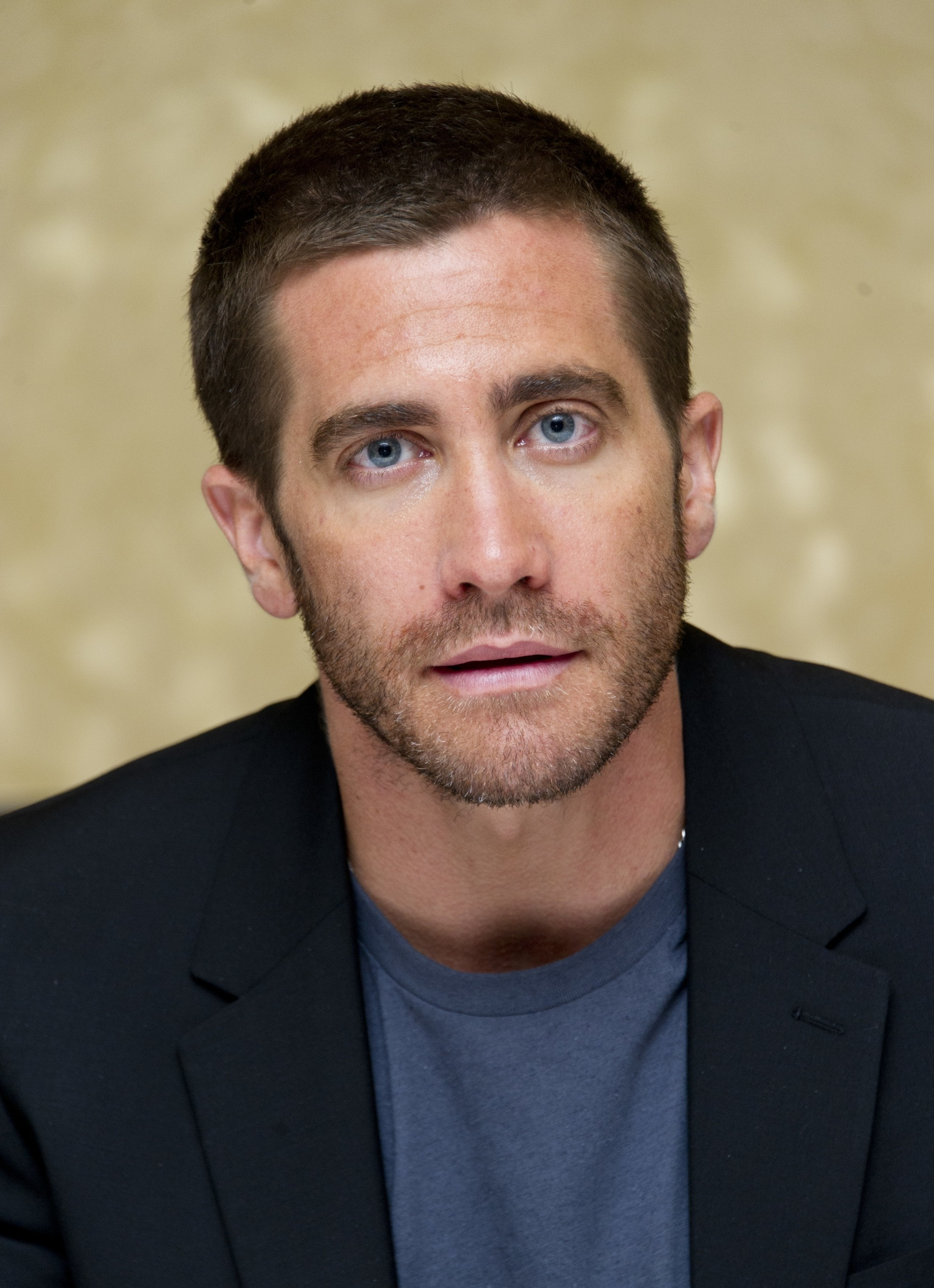 Hairstyles for receding hairline: Headshot of Jake Gyllenhaal with a crew cut haircut, wearing a blue t-shirt and black blazer