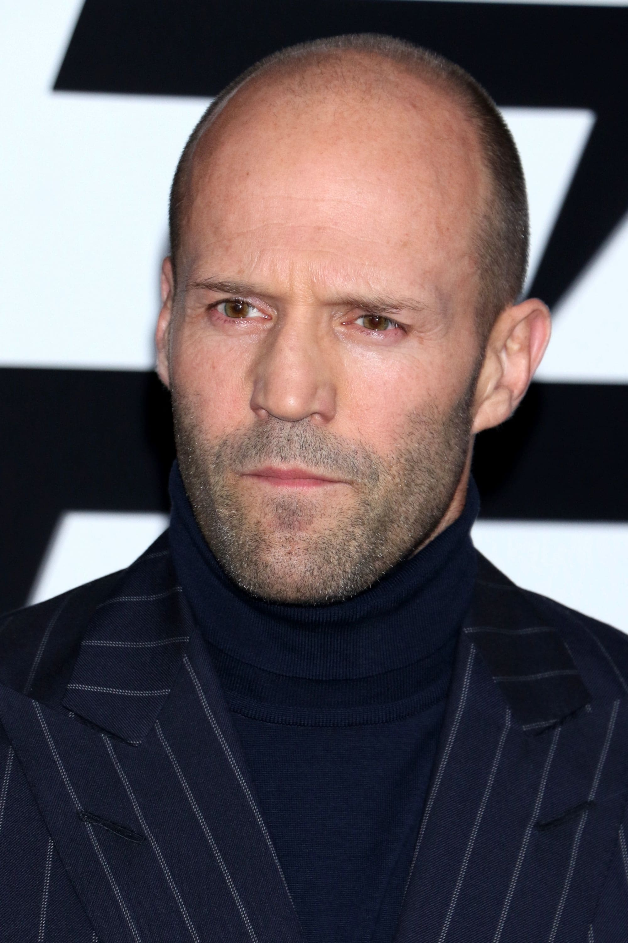 Hairstyles for receding hairline: Close-up headshot of Jason Statham with shaved head and stubble