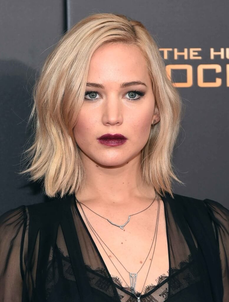 Jennifer Lawrence with a blonde wavy bob in side parting on the red carpet wearing a sheer black dress