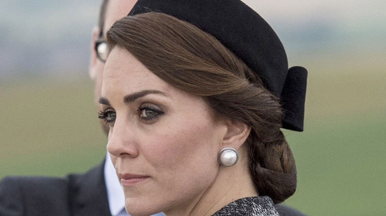 kate middleton wearing a grey outfit with her hair twisted into a low bun with a hairnet accessory and a black hat