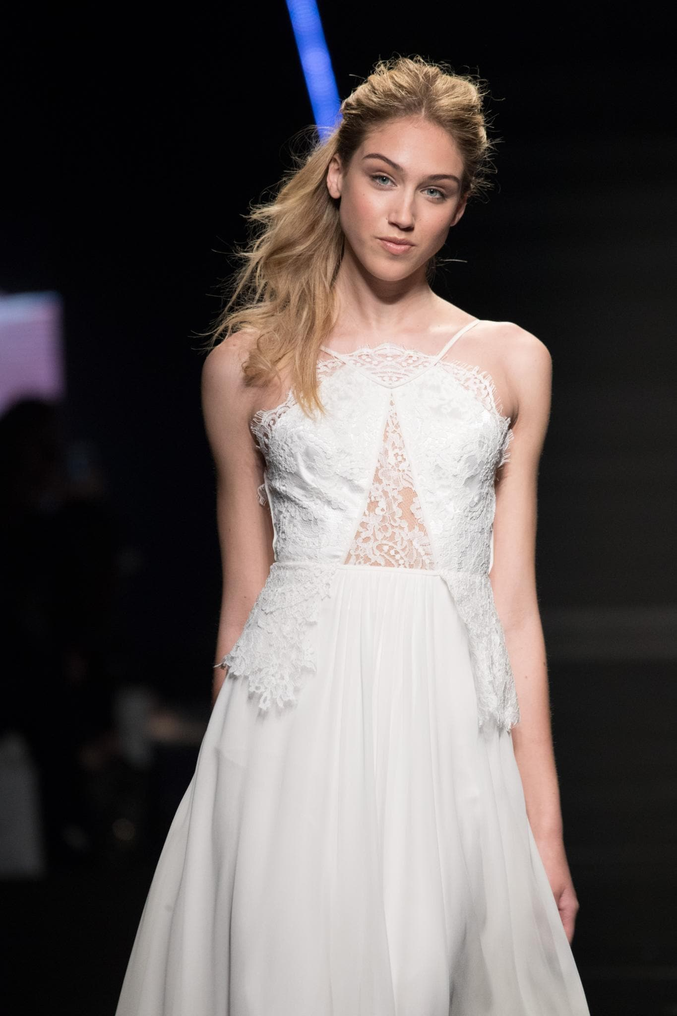 model on bridal runway with long dirty blonde hair in textured high ponytail with ends swept over one shoulder wearing wedding dress